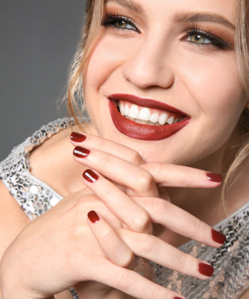 Fashionable young woman with beautiful manicure on grey background, closeup
